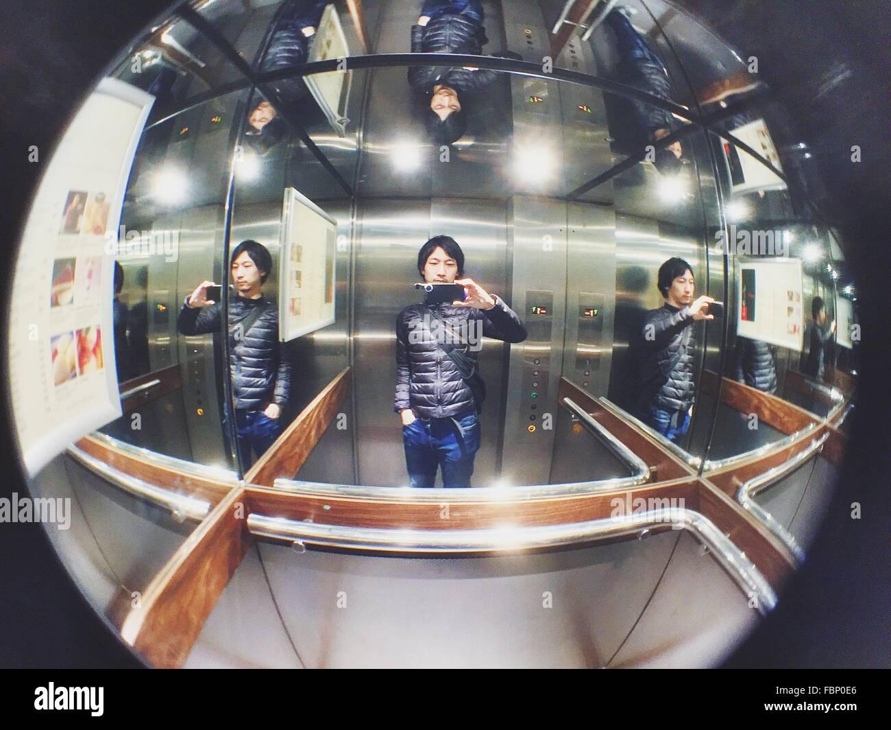 L'uomo prendendo Selfie in ascensore Immagini Stock