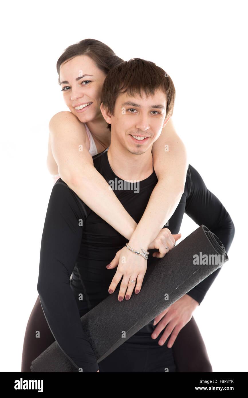 Ritratto di amare giovane sportivo con lo yoga, pilates mat prima della pratica sportiva, giocoso, sorridente giovane Immagini Stock