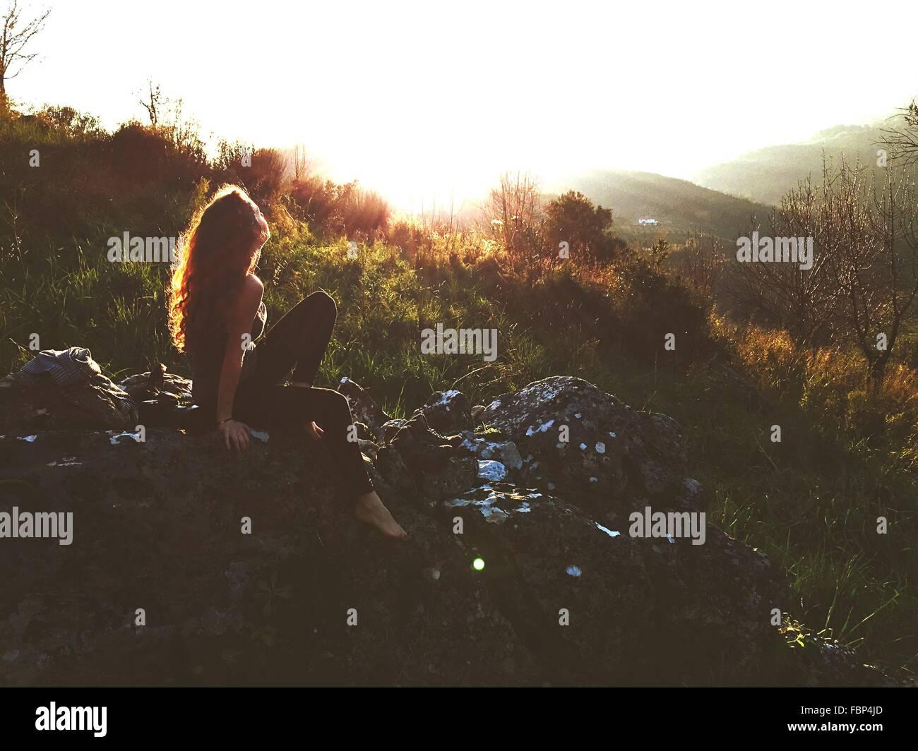 Side-View della giovane donna seduta su roccia Immagini Stock