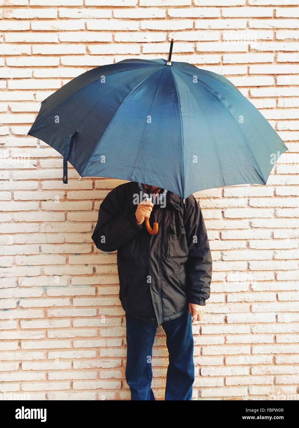 Uomo maturo Holding ombrello contro un muro di mattoni Immagini Stock