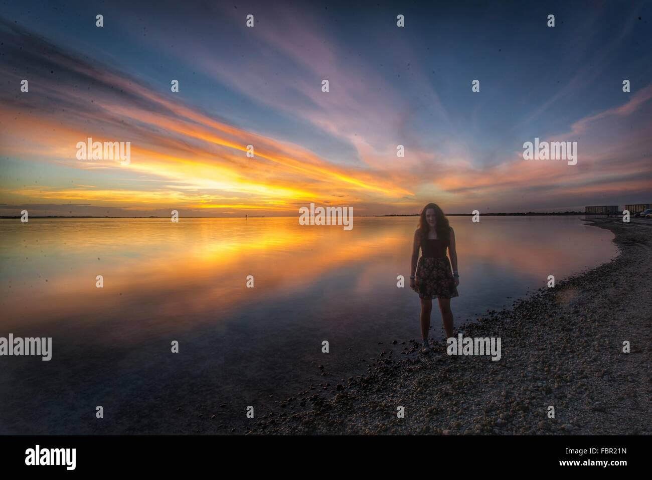 Per tutta la lunghezza della donna in piedi sulla spiaggia al tramonto Immagini Stock