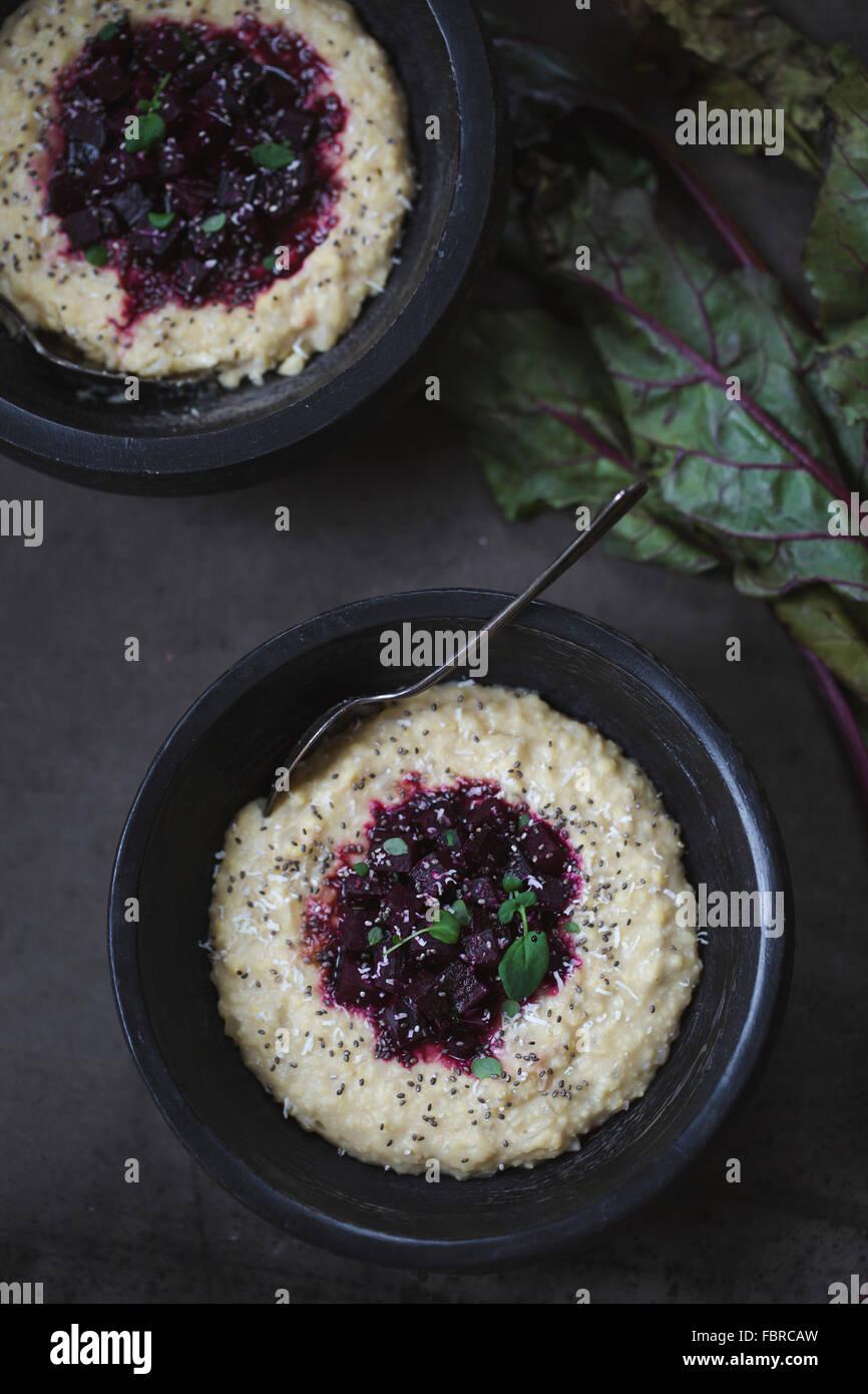 Due ciotole di miglio di polenta condito con barbabietole rosse, chia semi e foglie microgreen. Immagini Stock