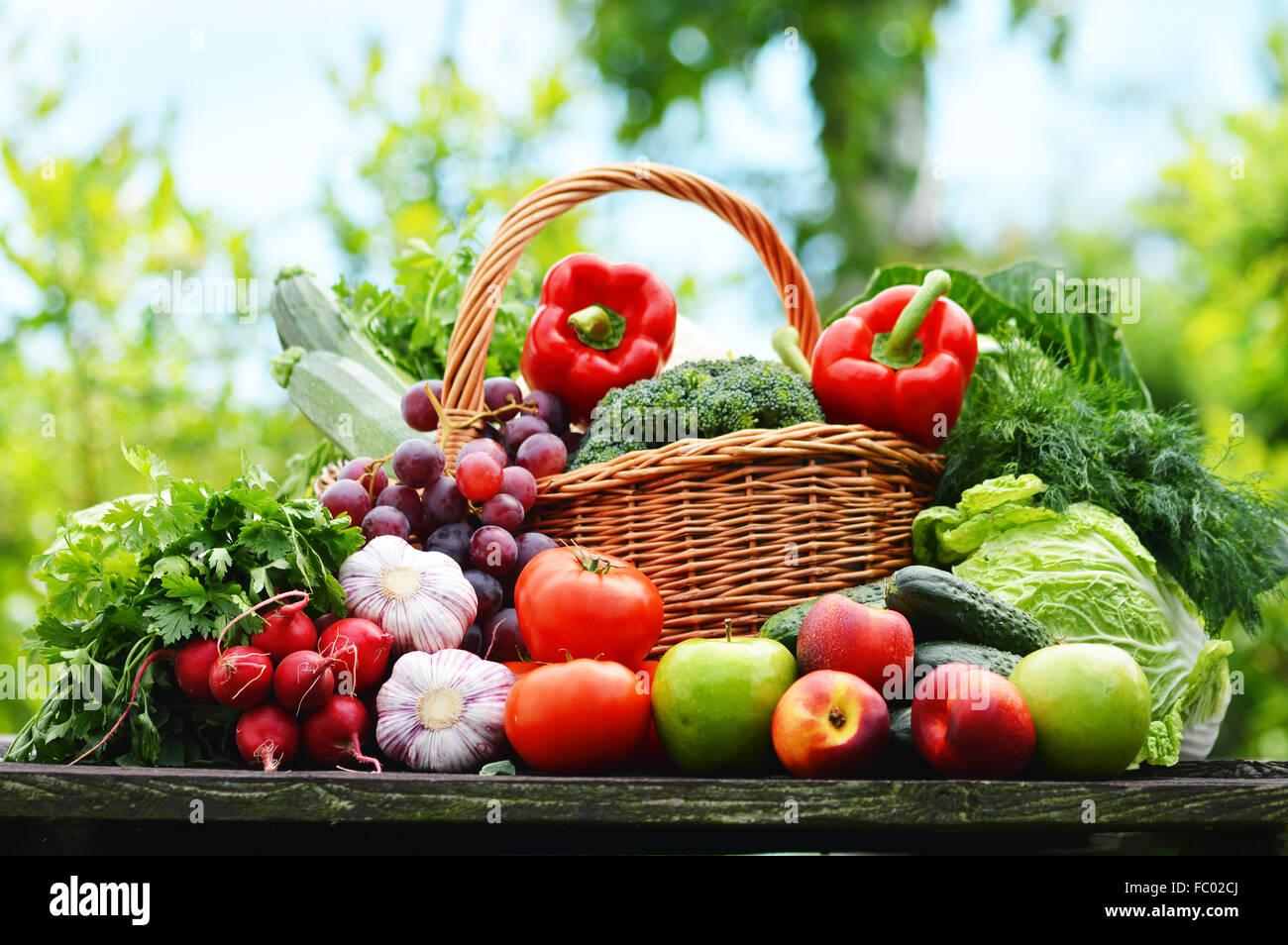 Fresche verdure organiche nel cesto di vimini in giardino. Immagini Stock