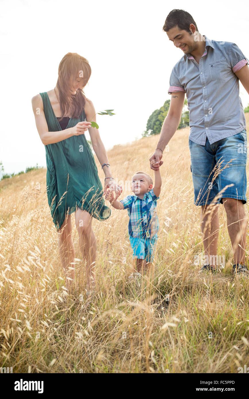 Genitori felici camminare con il giovane figlio nel campo Immagini Stock