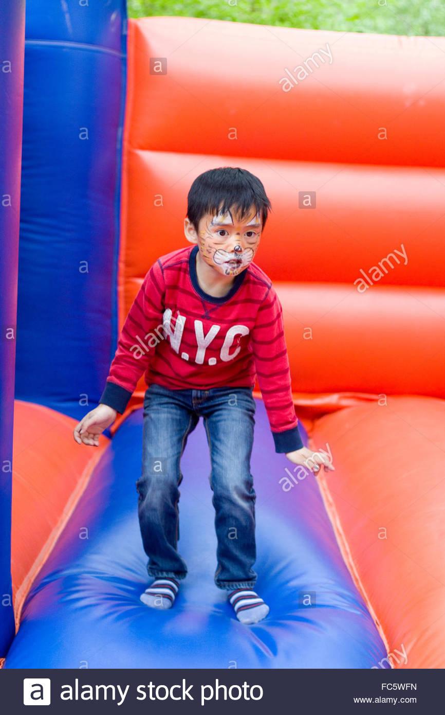 Little Boy sul castello gonfiabile Foto Stock