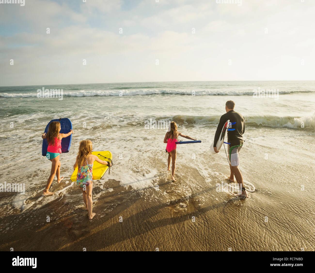 Padre caucasica e figlie giocando in onde sulla spiaggia Foto Stock
