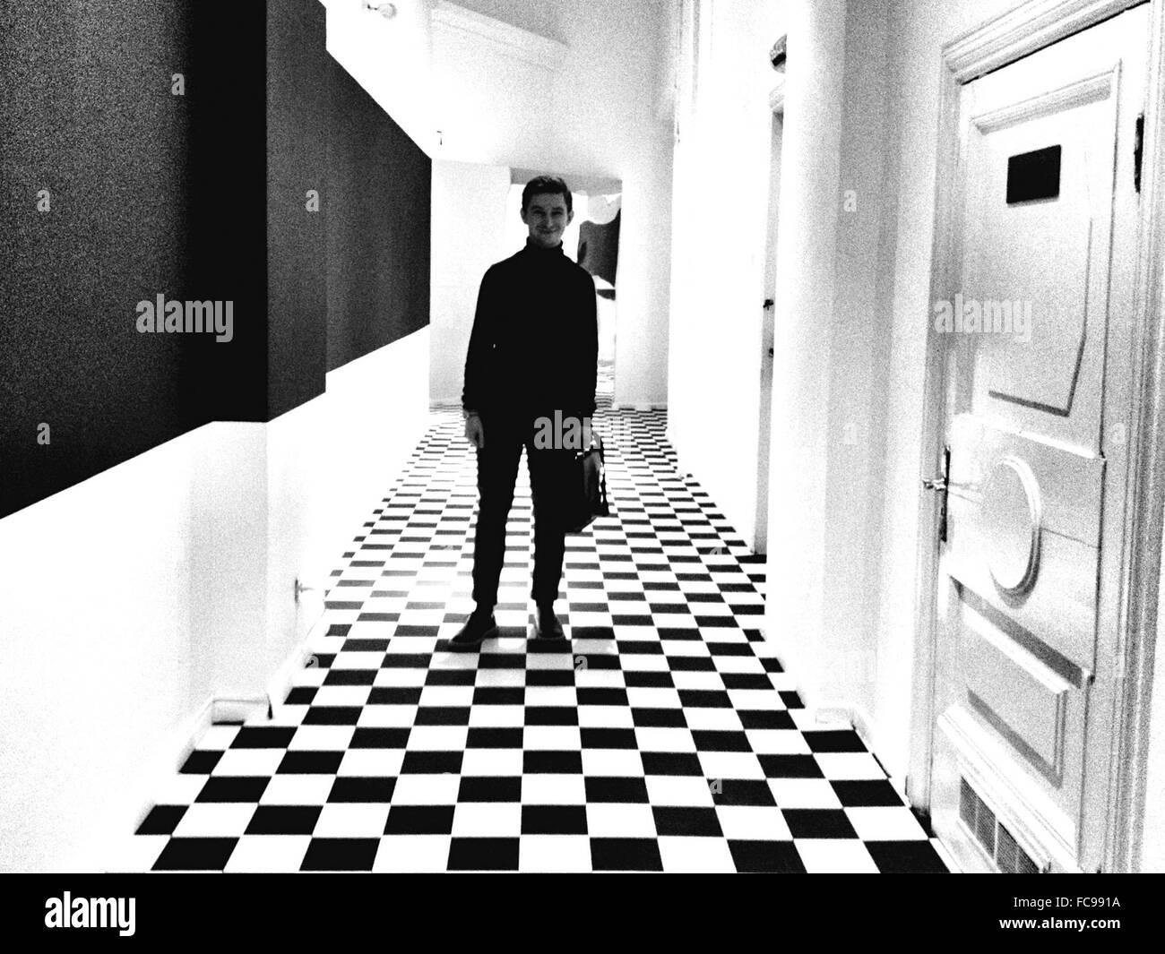 Lunghezza completa di uomo sorridente in piedi in corridoio Immagini Stock
