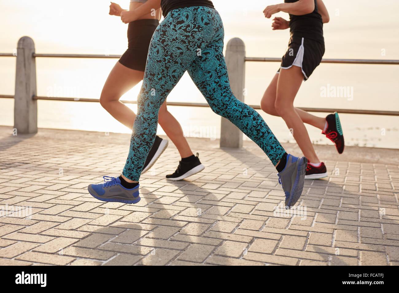 Immagine ritagliata di giovani che corre lungo il mare. Gruppo Fitness facendo esecuzione di allenamento insieme Immagini Stock
