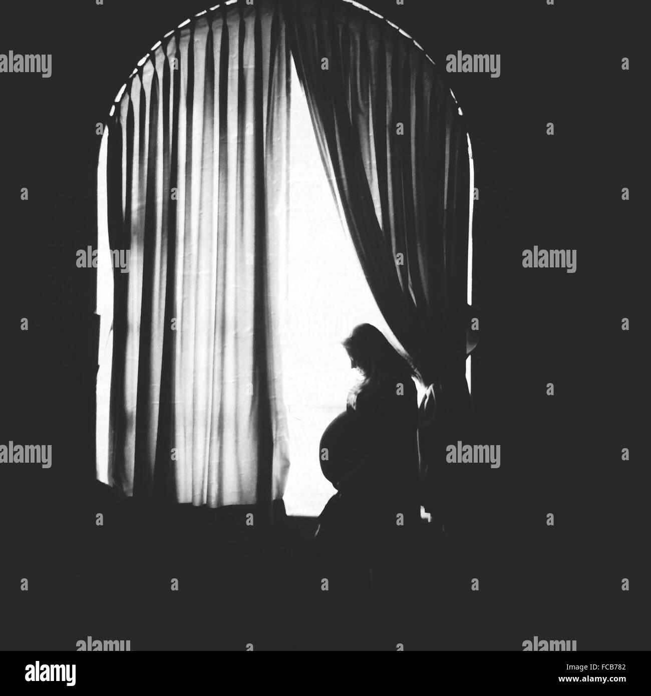 Vista laterale di una donna incinta in piedi alla finestra Immagini Stock
