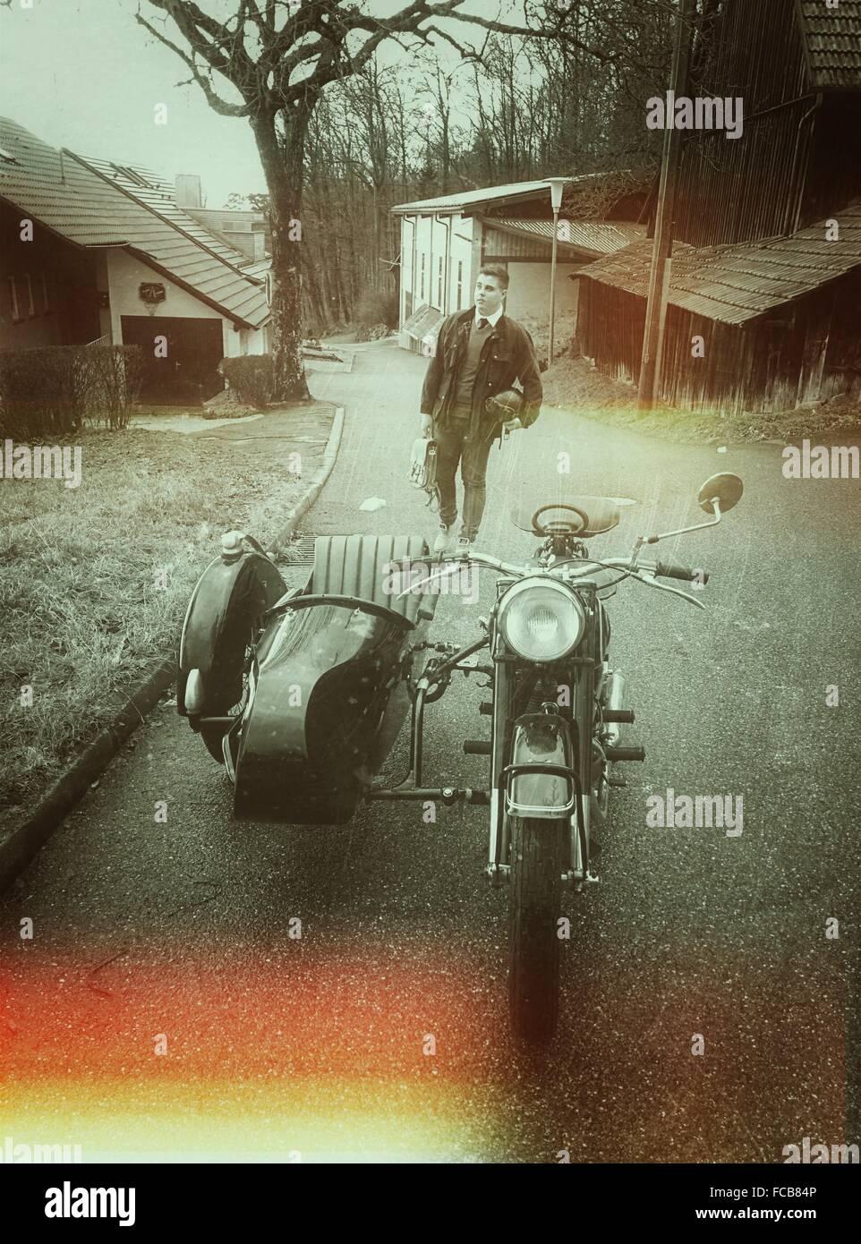Giovane uomo a camminare sulla strada con la moto in primo piano Immagini Stock