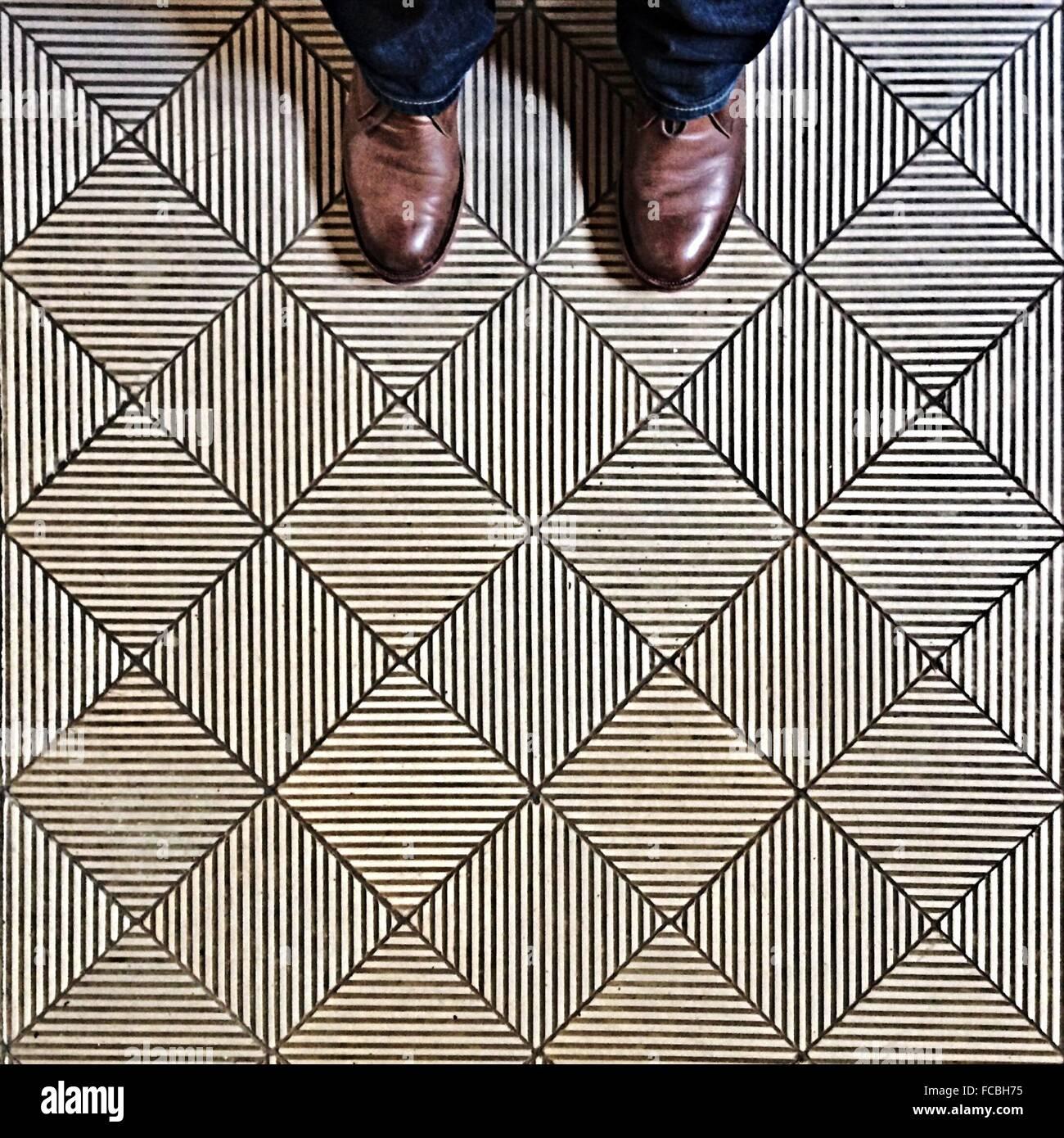 L'uomo con i piedi sul pavimento Immagini Stock