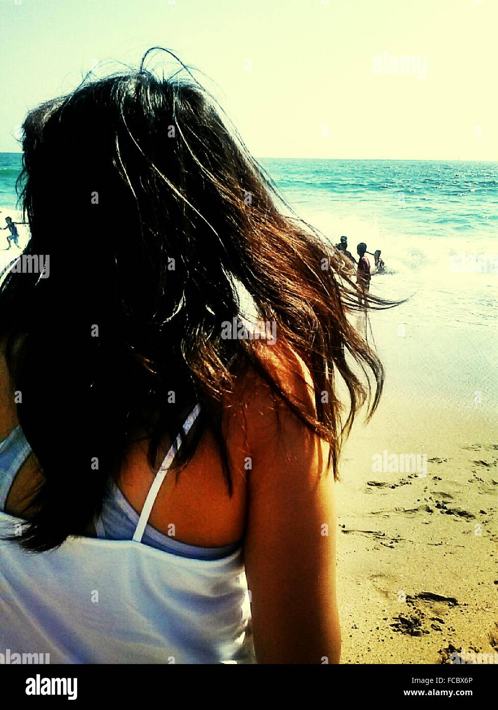 Donna in piedi sulla spiaggia Immagini Stock