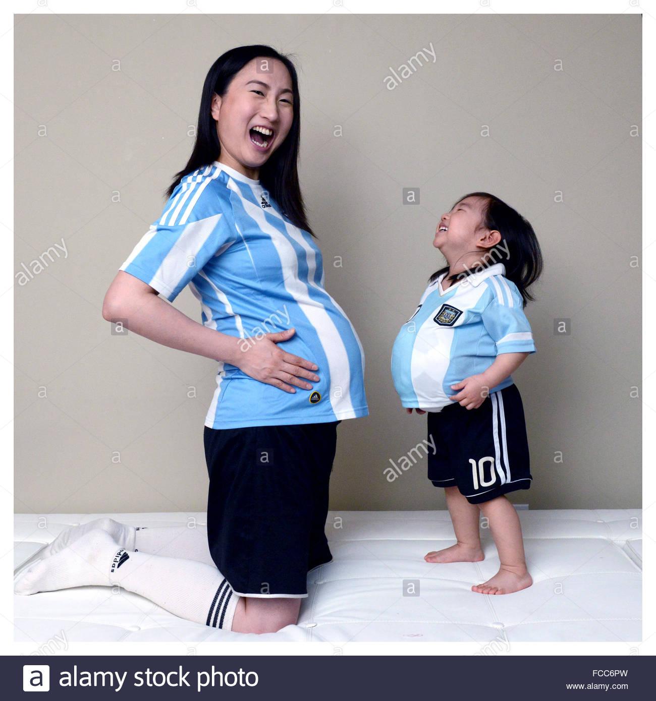 Felice figlia imitando la gravidanza madre a casa Immagini Stock