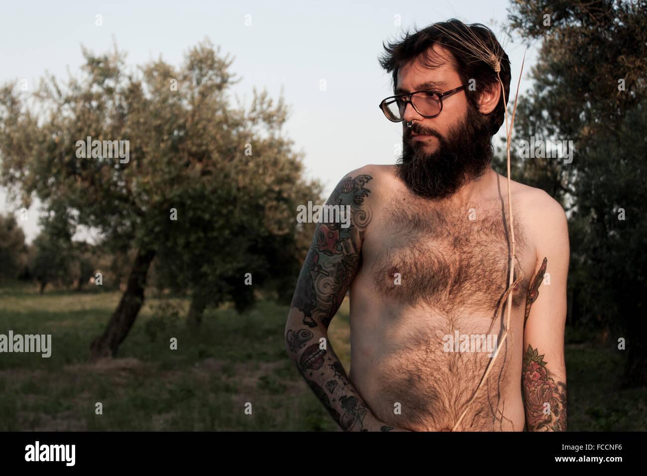 Shirtless uomo in piedi sul campo erboso Immagini Stock