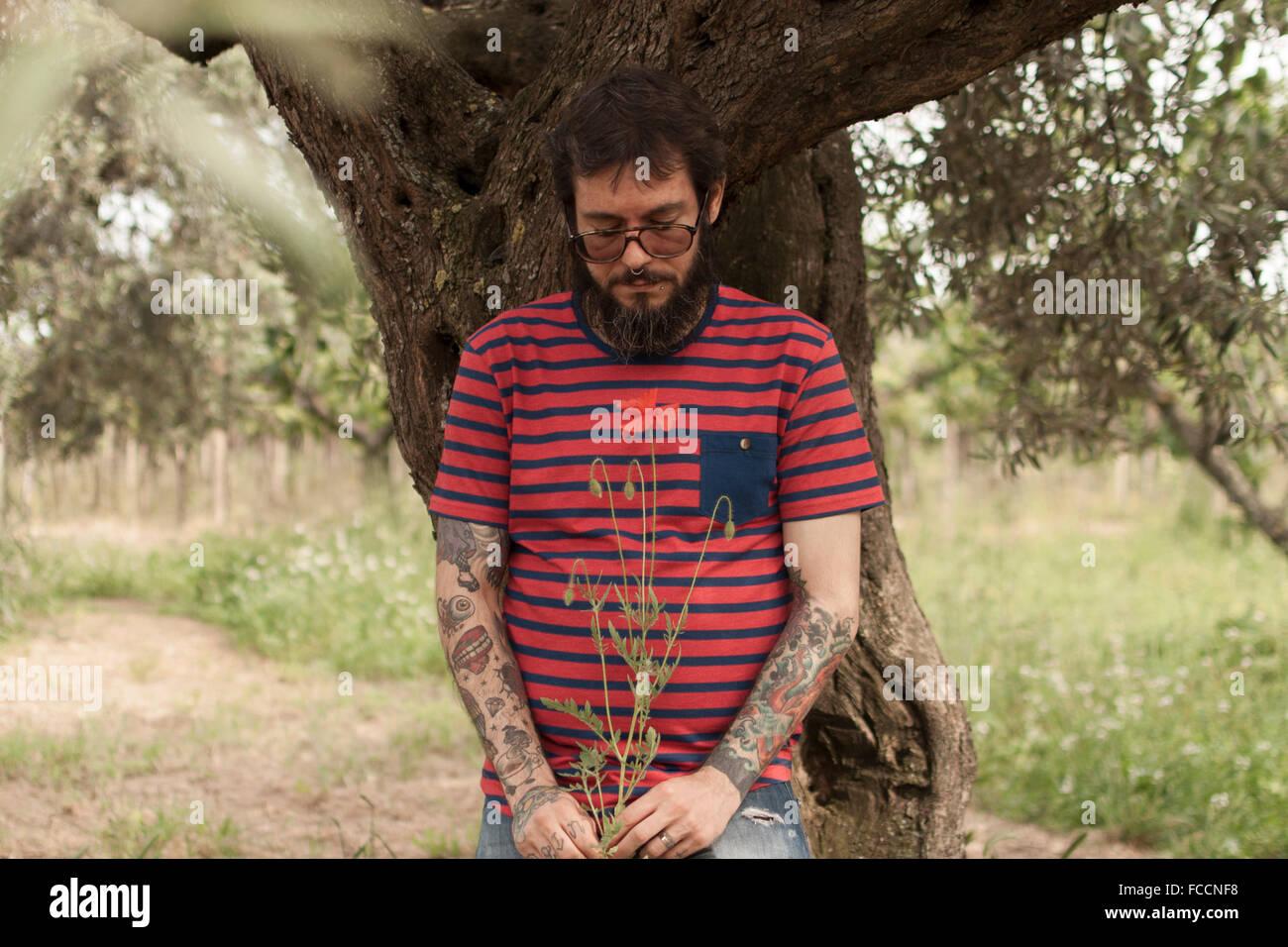 Uomo con fiore mentre si sta in piedi sul campo Immagini Stock