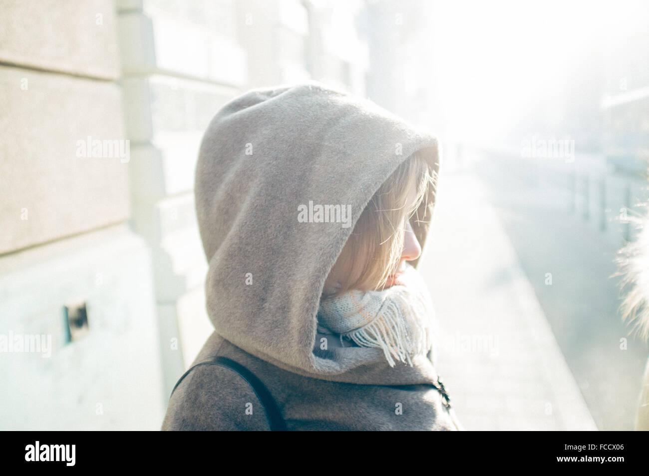 Vista laterale della donna che indossa il cofano Immagini Stock