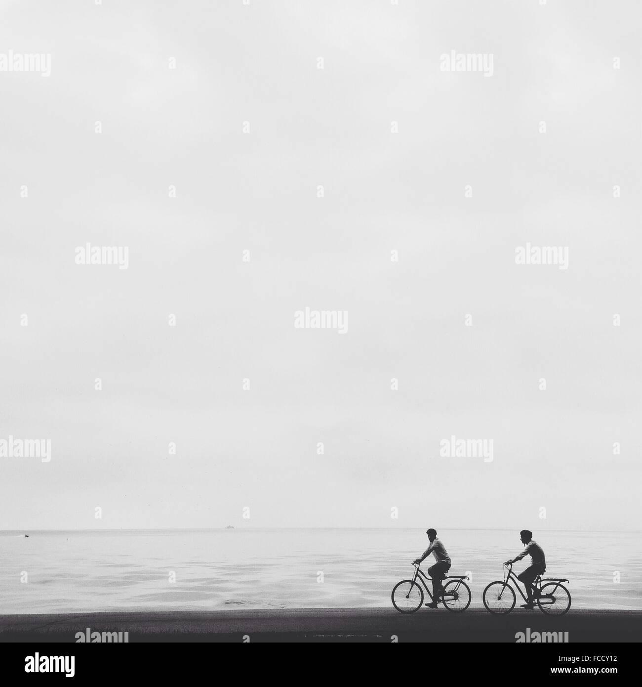 Gli uomini Bicicletta Equitazione sulla spiaggia contro il cielo chiaro Immagini Stock