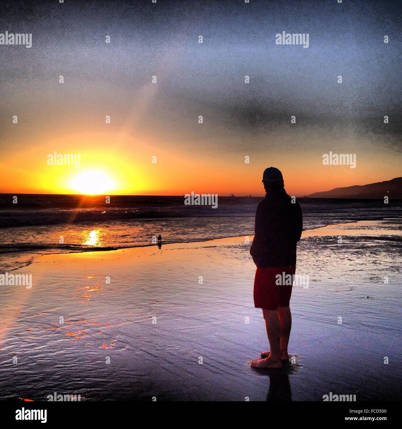 Lunghezza piena vista posteriore dell'uomo in piedi sulla spiaggia contro il cielo durante il tramonto Immagini Stock