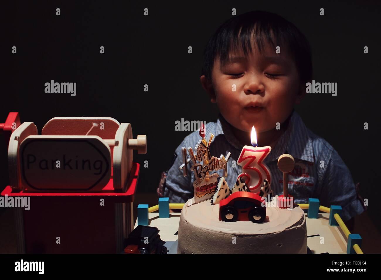 Ragazzo carino con occhio chiuso compleanno di soffiaggio candela sulla torta in camera oscura Immagini Stock