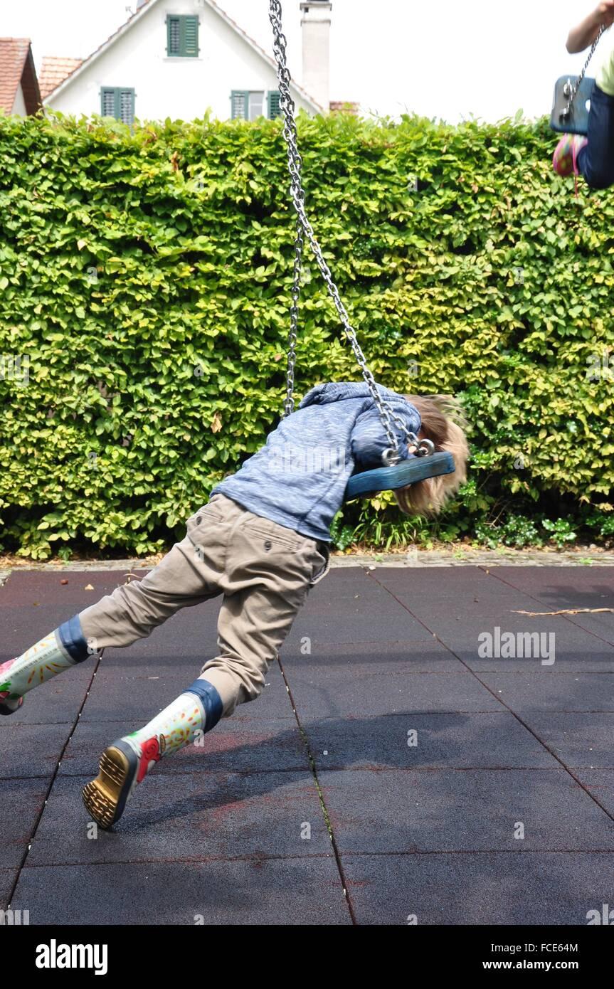 Vista laterale di un ragazzo su Swing sul parco giochi Immagini Stock