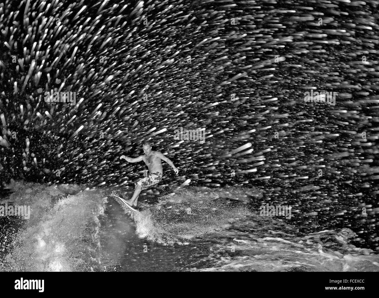L'uomo Surf in mare di notte Immagini Stock