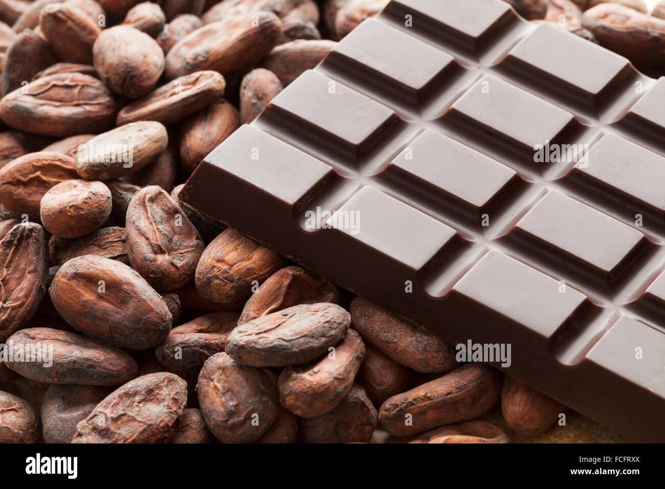 Barretta di cioccolato con materie prime fave di cacao Immagini Stock