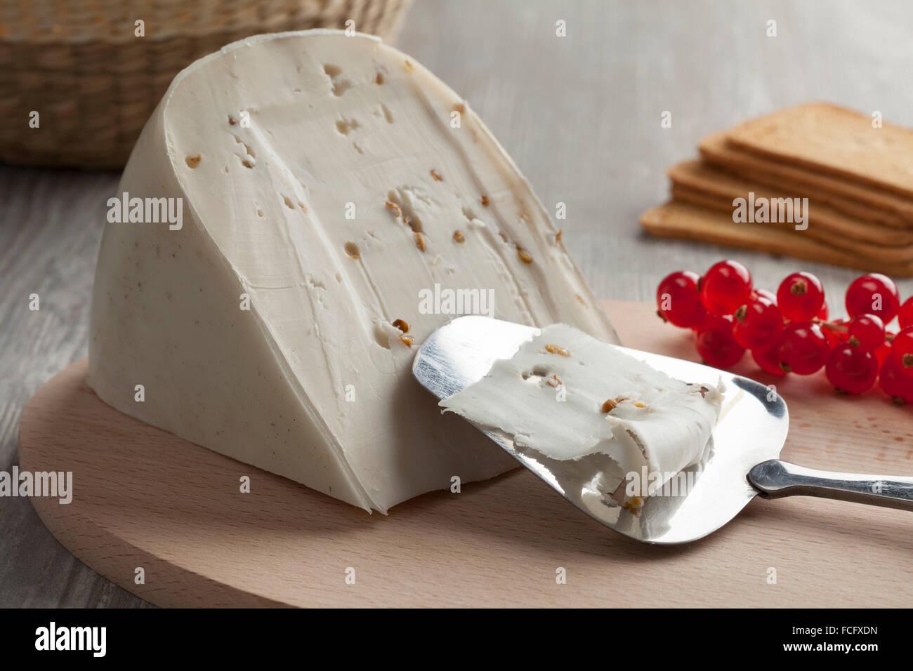 Olandese di formaggio di capra con semi di coriandolo e di fieno greco con un'affettatrice come dessert Immagini Stock