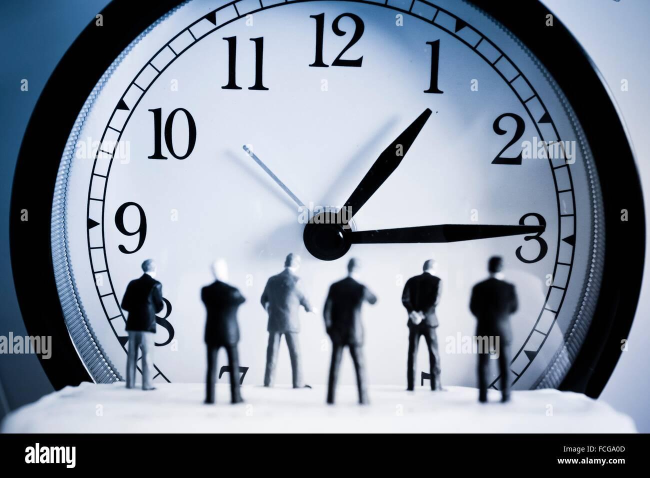 Concetto di tempo. Gli uomini indietro di fronte a un orologio. Immagini Stock