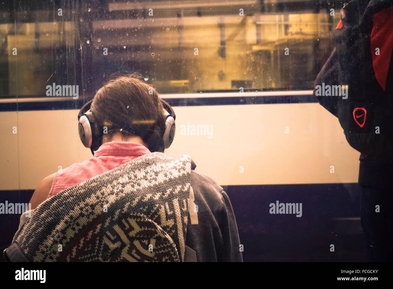 Giovane donna torna con le cuffie sull'ascolto di musica. Sullo sfondo la vettura di un treno in movimento. Immagini Stock