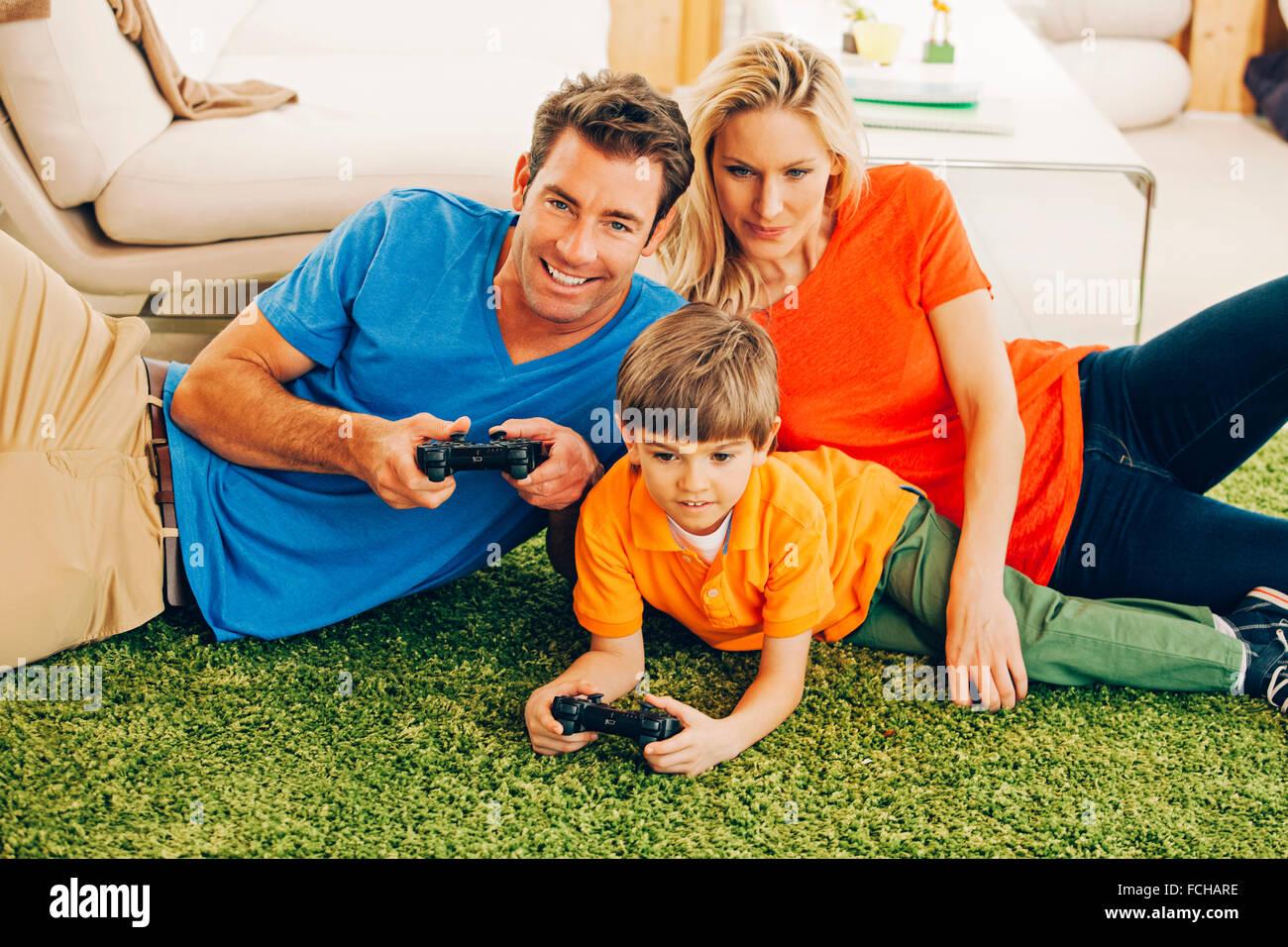 Famiglia di tre persone la riproduzione del video gioco in soggiorno Immagini Stock