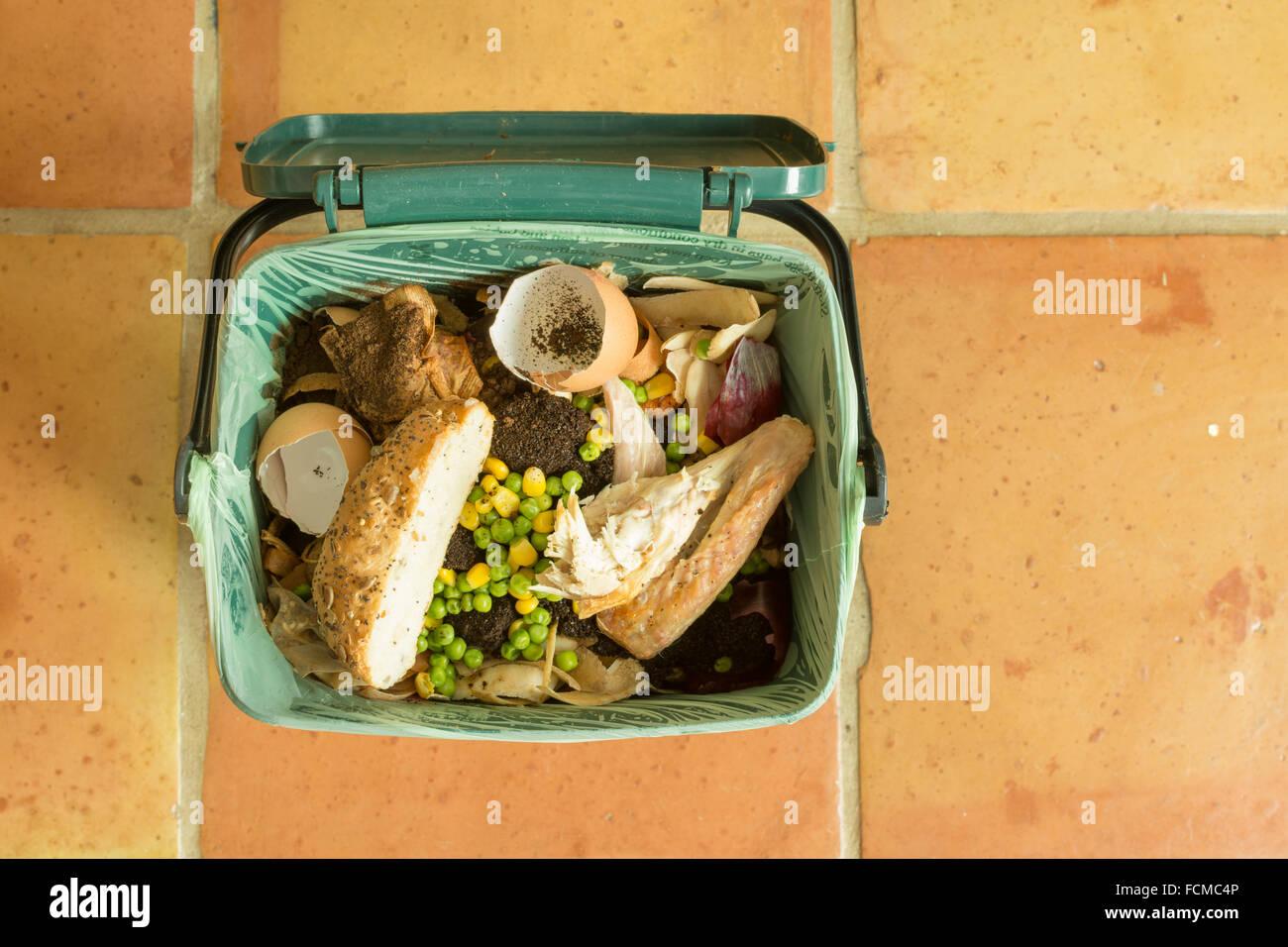 I rifiuti alimentari - coperta di riciclo alimentare caddy piena di rifiuti di cucina con carne e pane Immagini Stock