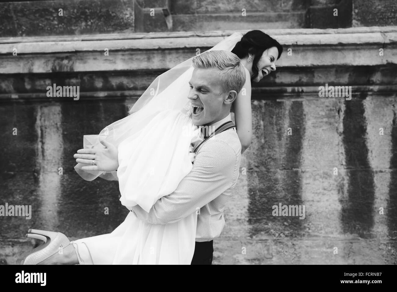 Lo sposo porta sposa nelle sue braccia Immagini Stock