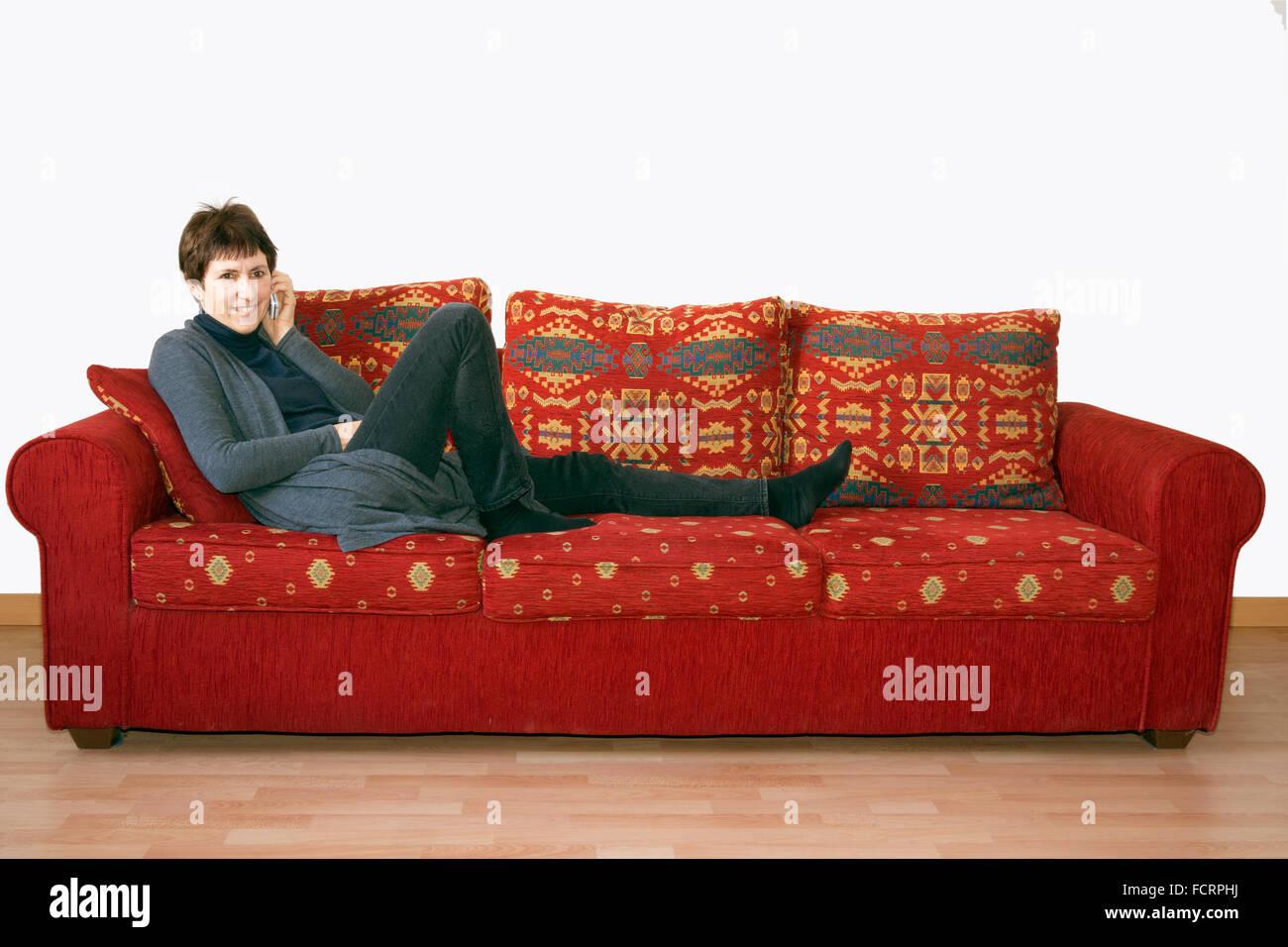 Donna anziana spettegolare sul telefono, sul divano. Immagini Stock