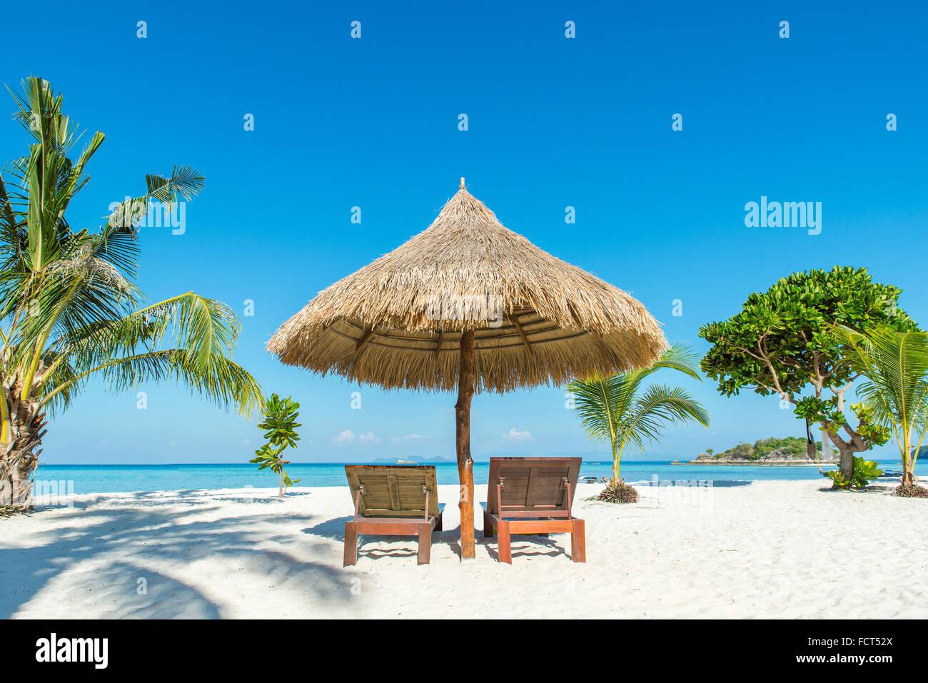 Estate, Viaggi, vacanze e concetto di vacanza - Sedie a sdraio e ombrellone sull isola di Phuket, Tailandia Foto Stock