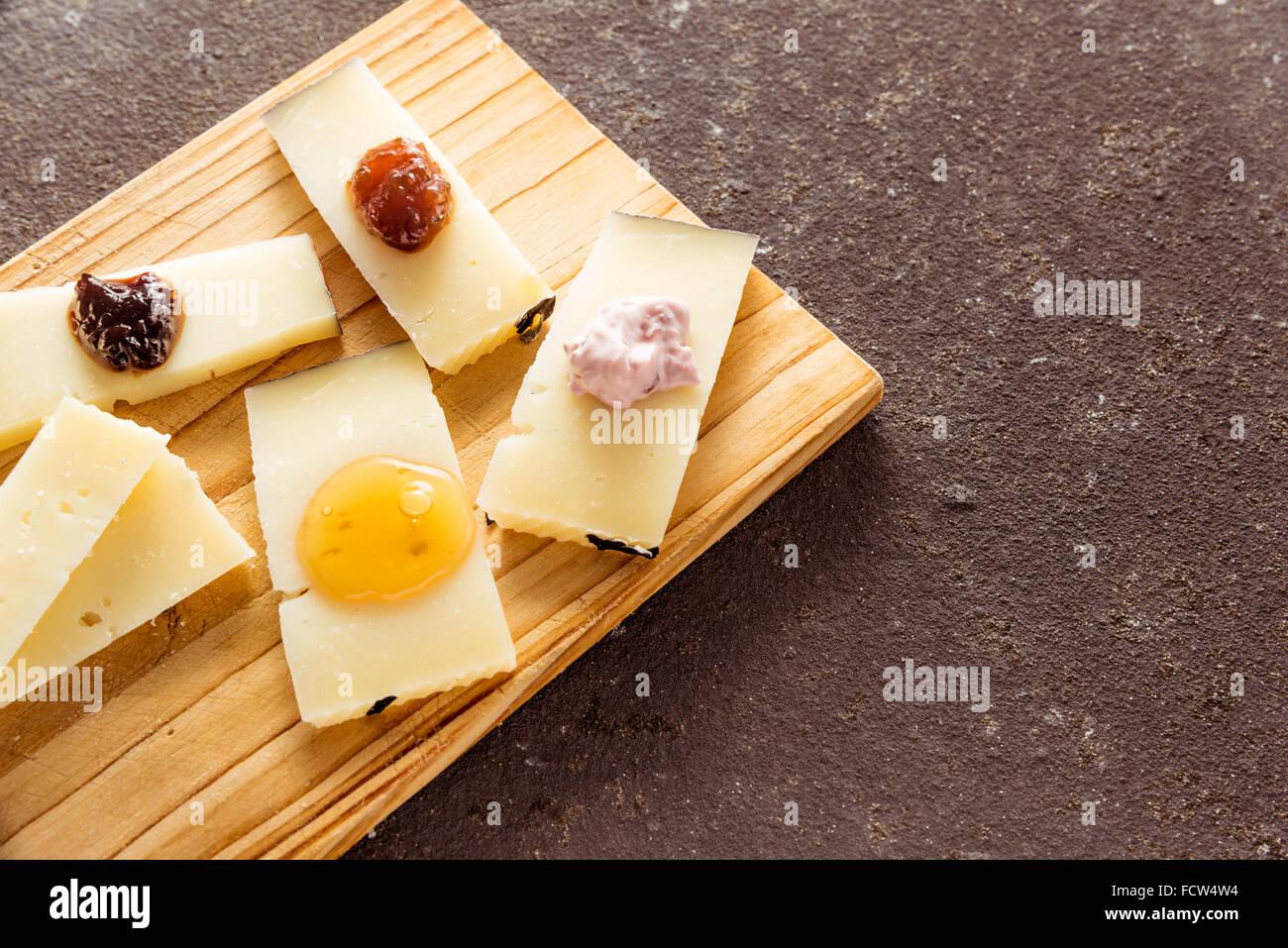 Una composizione di formaggi italiani pecorino fette con marmellate di sapori diversi su un tagliere di legno Immagini Stock