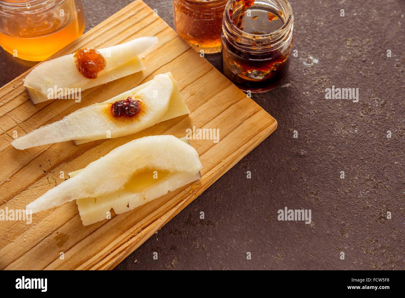 Una composizione di formaggi italiani pecorino fette con marmellate e pere su un tagliere di legno Immagini Stock