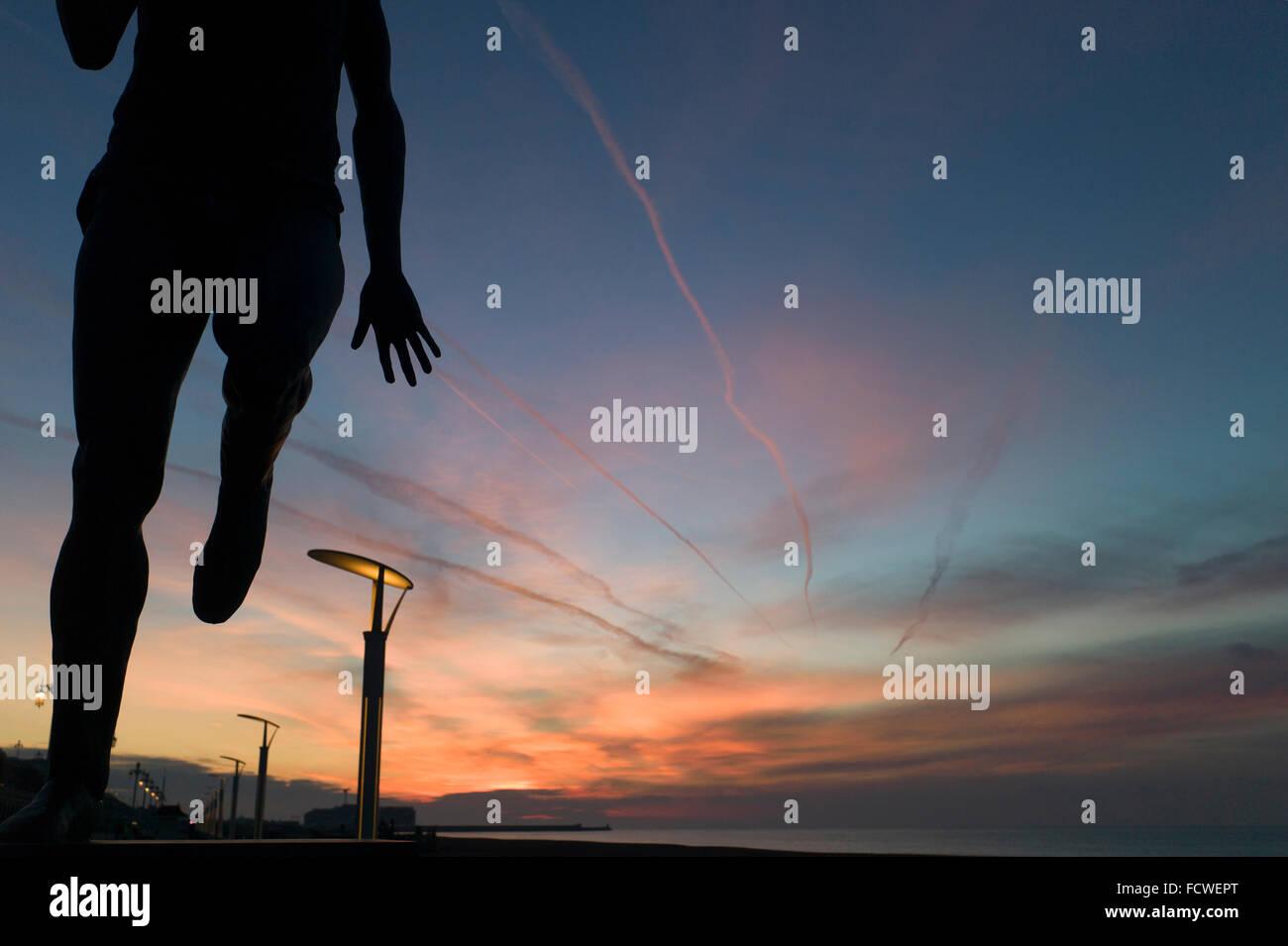 Silhouette della statua di Steve Ovett, runner, Brighton Seafront, allo spuntar del giorno, drammatica sunrise sky Immagini Stock