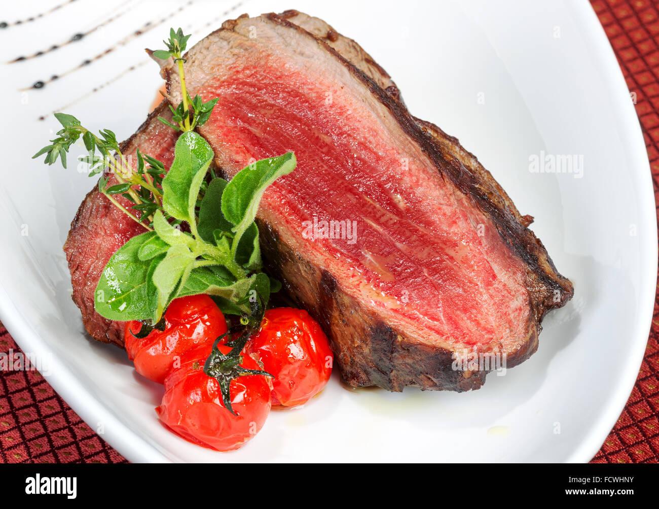 Di medie bistecche alla griglia e saporita salsa di pomodoro Immagini Stock