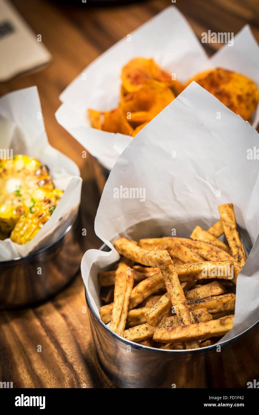 Rustico patatine fritte e altri semplici snack alimentare sul tavolo Immagini Stock
