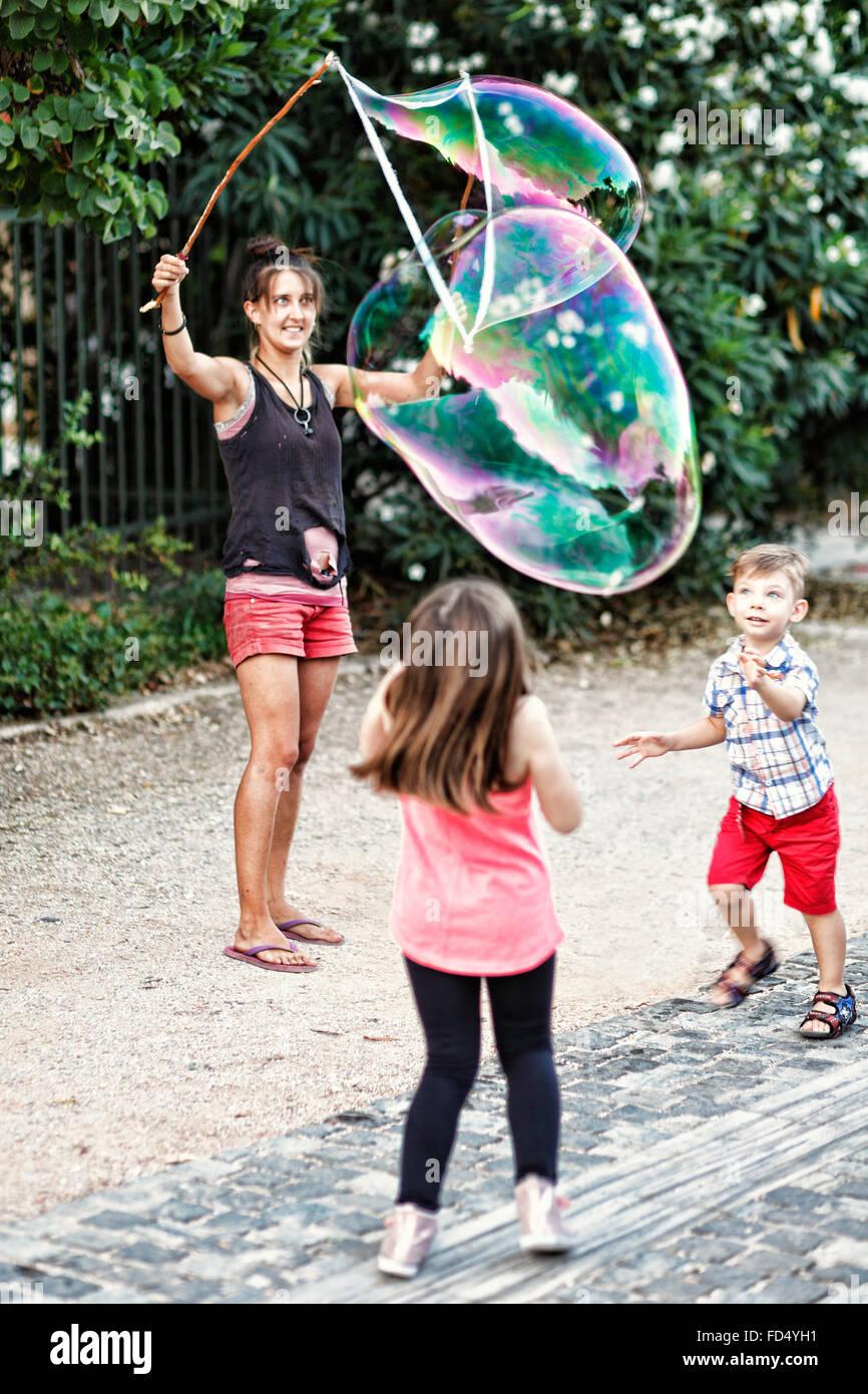 I bambini a giocare con le bolle di gigante per le strade di Atene, Grecia Immagini Stock