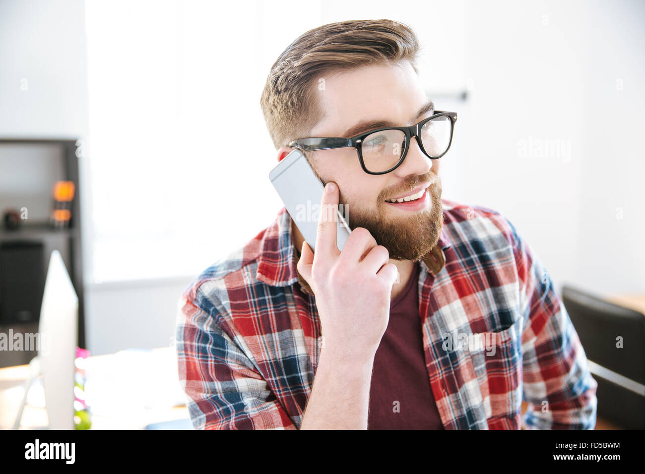 Felice attraente giovane uomo con la barba in plaid shirt e bicchieri parlando al cellulare in ufficio Immagini Stock
