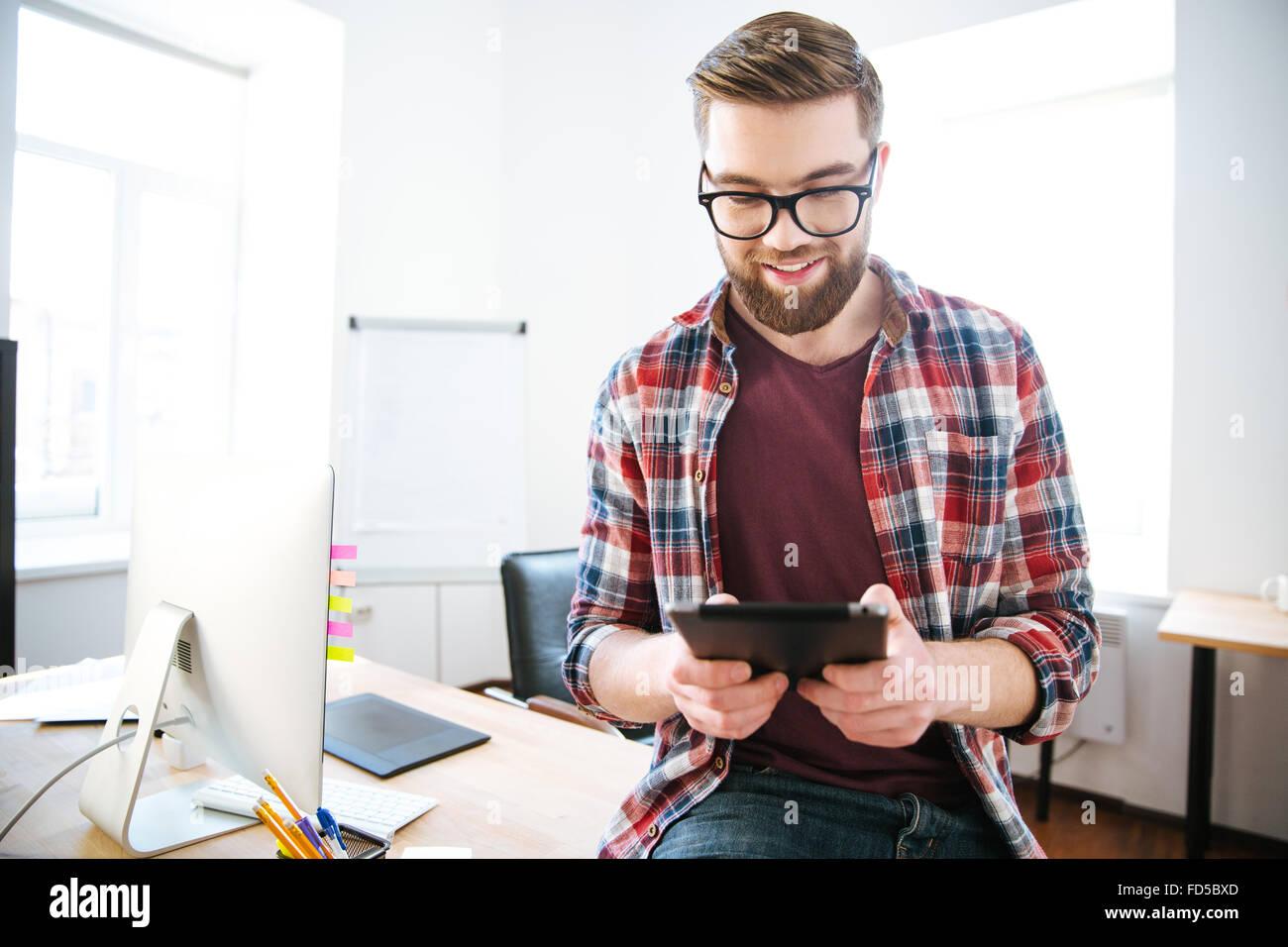 Felice uomo bello con la barba in plaid shirt e bicchieri di seduta sul tavolo in ufficio e utilizzando tablet Immagini Stock