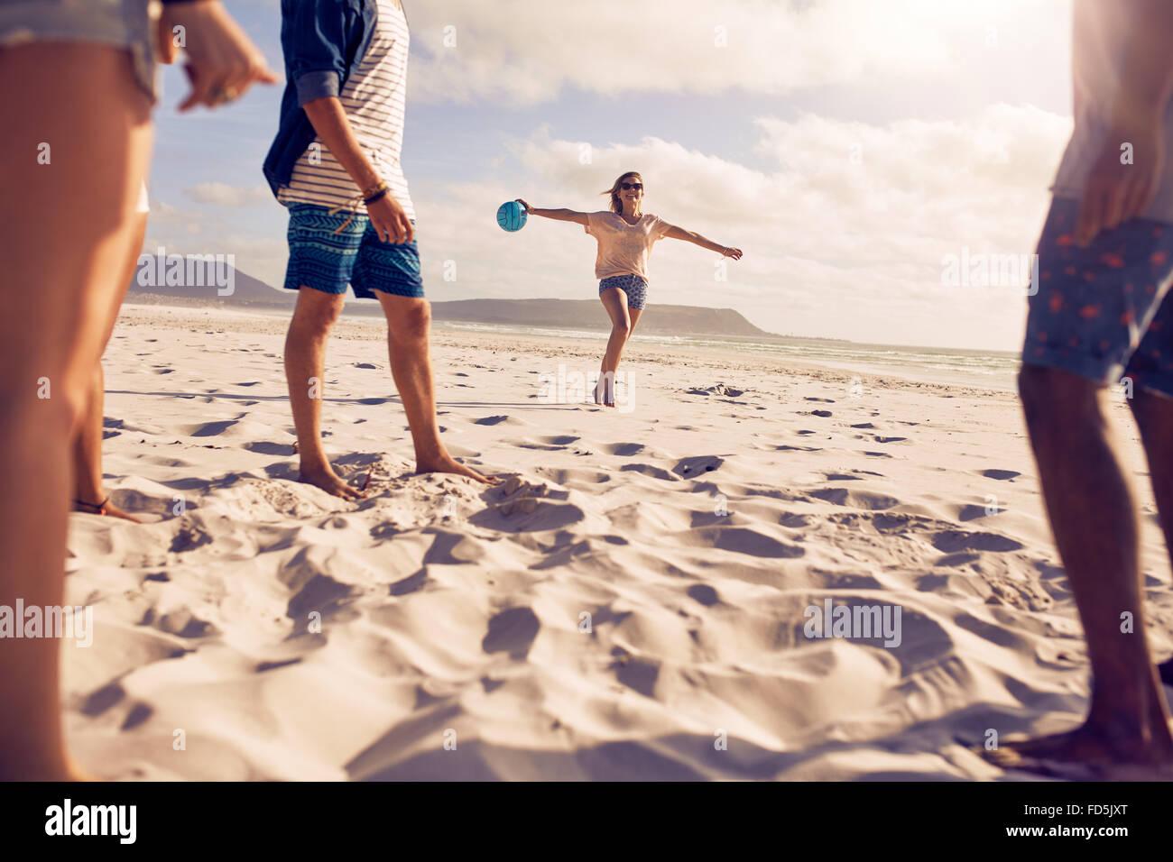 Bassa angolazione della giovane donna in esecuzione sulla spiaggia con una palla con i suoi amici in piedi di fronte. Immagini Stock