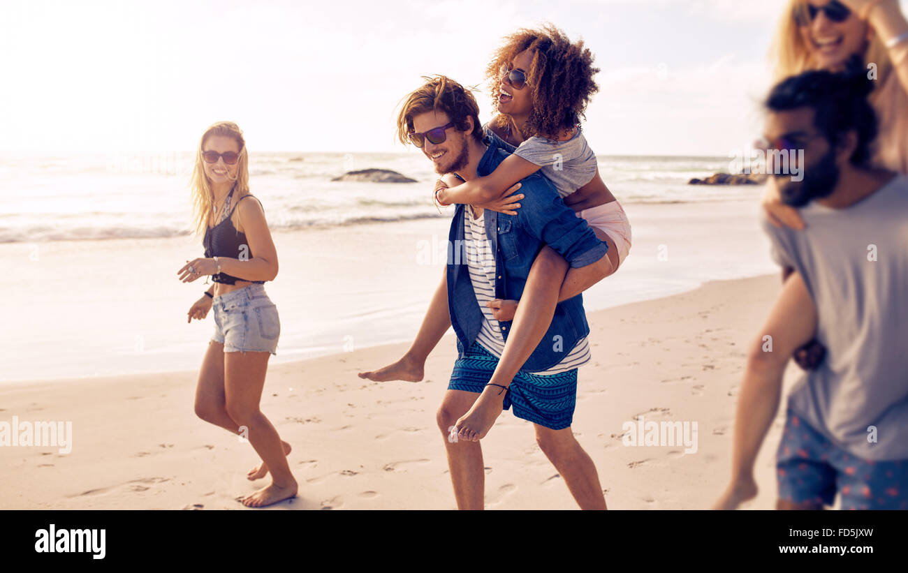 Due giovani felici gli uomini dando loro fidanzate piggyback passeggiate sulla spiaggia. Gruppo di amici godendo Immagini Stock