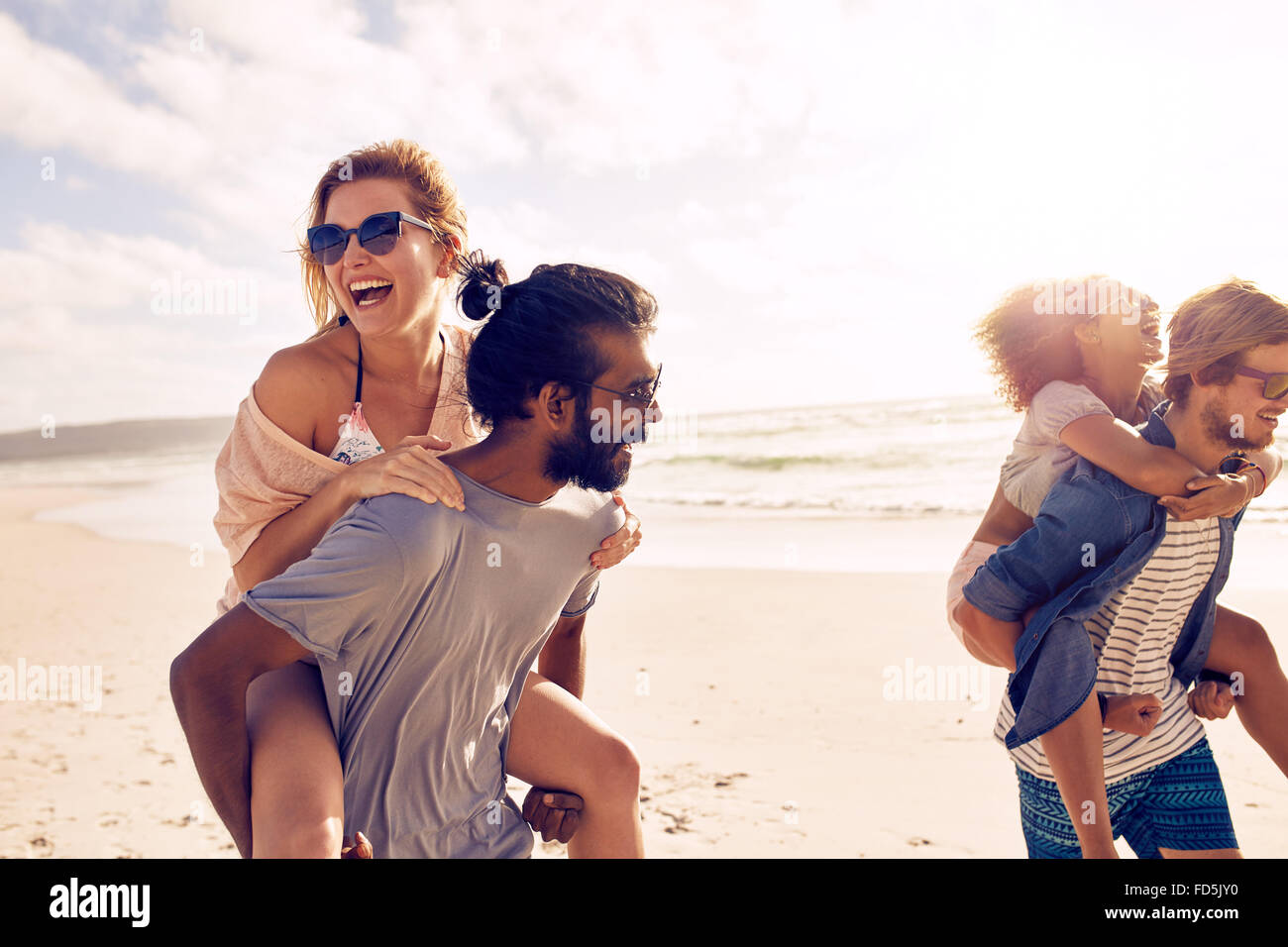 Felice giovani uomini dando piggyback ride per donne sulla spiaggia. Diversi gruppi di giovani aventi il divertimento Immagini Stock