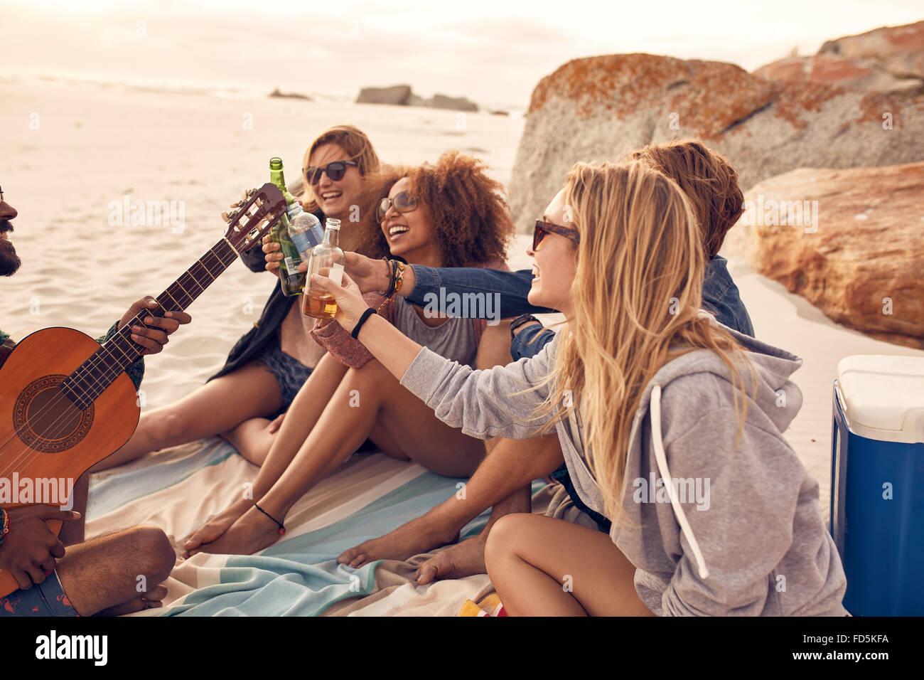 Gruppo di multi-etnico giovani birre di tostatura sulla spiaggia. Gruppo di amici di trascorrere del tempo insieme Immagini Stock