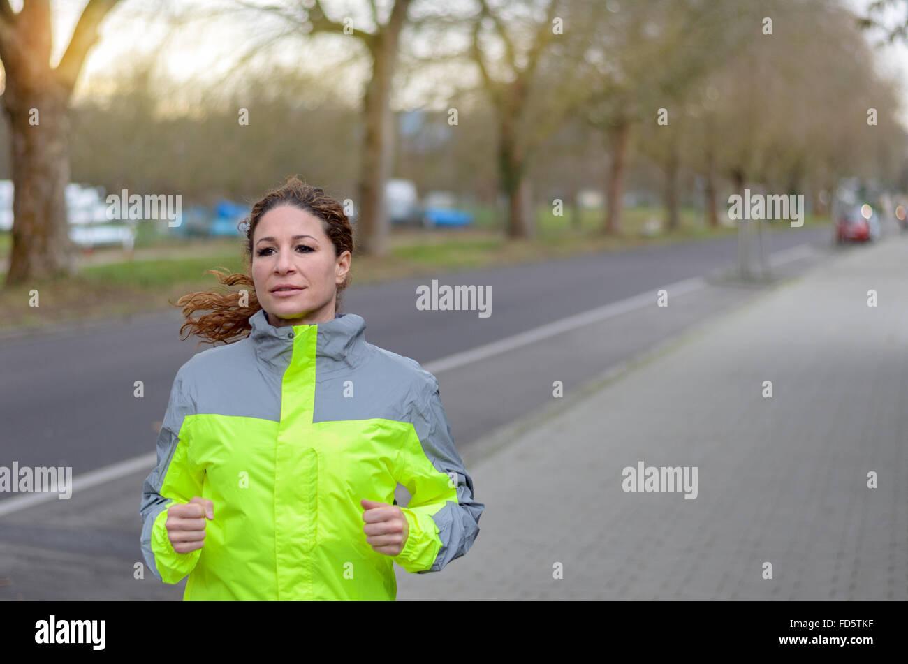 Determinata donna jogging lungo una strada in un GIUBBETTO ALTA VISIBILITA passando davanti alla telecamera con Immagini Stock
