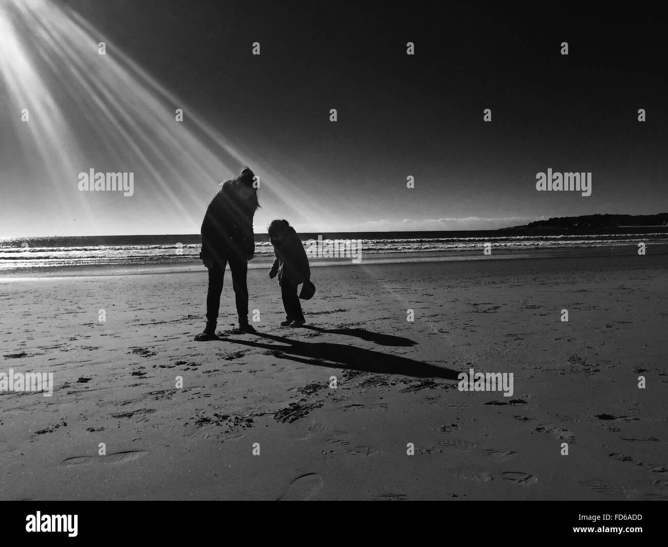 Madre con sua figlia permanente sulla spiaggia Immagini Stock