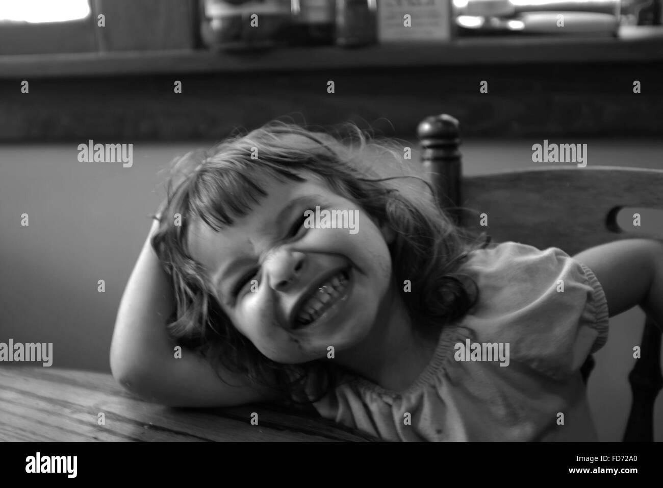 Felice ragazza rendendo la faccia mentre è seduto su una sedia Immagini Stock