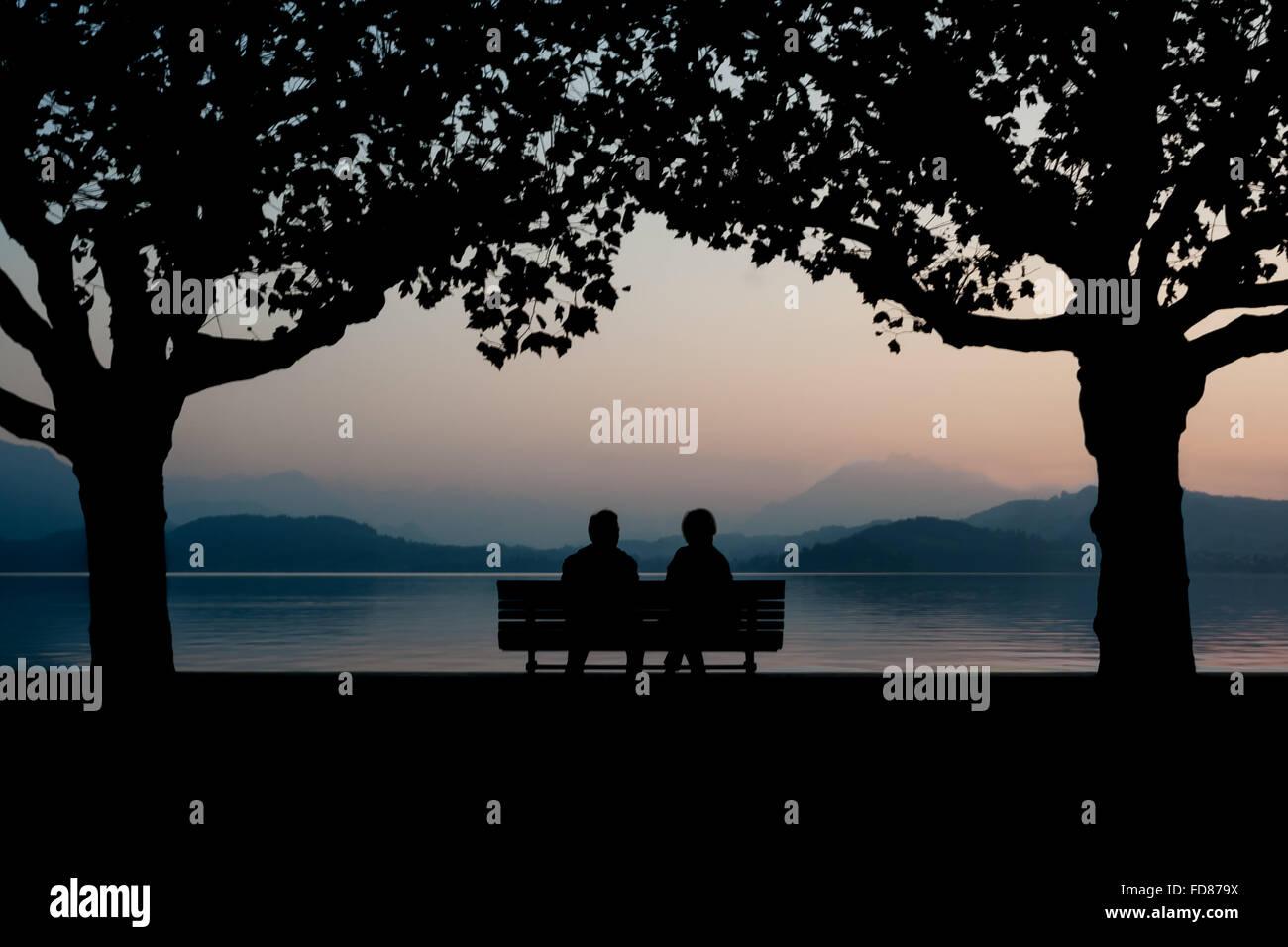 Silhouette giovane seduto su un banco di lavoro dal lago calmo al crepuscolo Immagini Stock